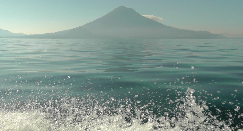 Spray from the boat I was in dances before a glassy lake and hulking volcano. Heavenly.