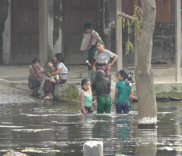 Local children splashing around in Lago de Atitlán near Santiago