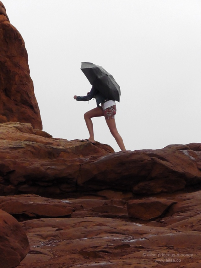 foggy arches national park girl umbrella monsoon season utah walking climbing